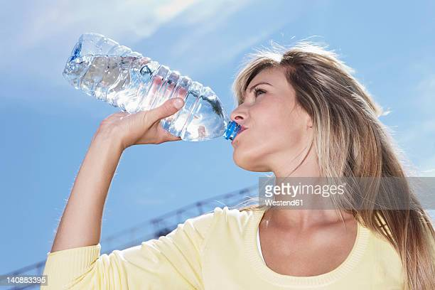 germany, cologne, young woman drinking water - mineral water stock photos and pictures