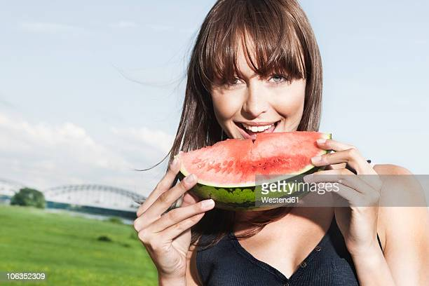 Germany, Cologne, Young woman eating watermelon, portrait