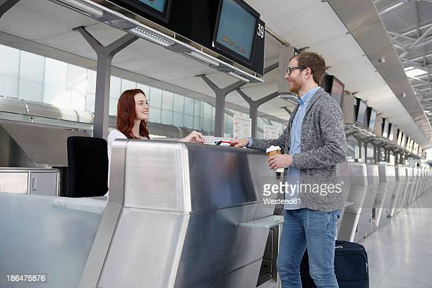Germany, Cologne, Young woman giving ticket to mid adult man