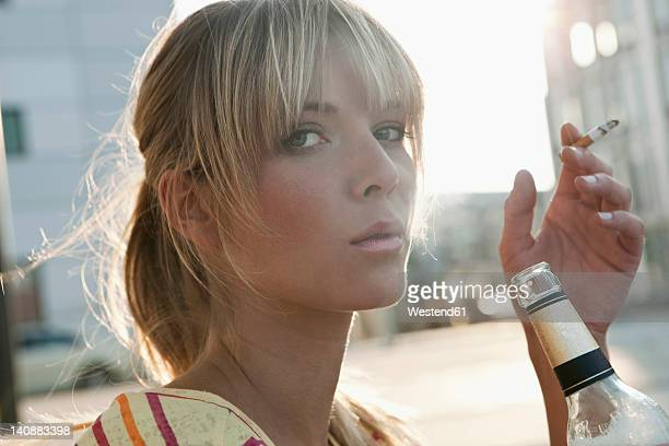 germany, cologne, young woman holding beer bottle and smoking - beautiful women smoking cigarettes stock photos and pictures