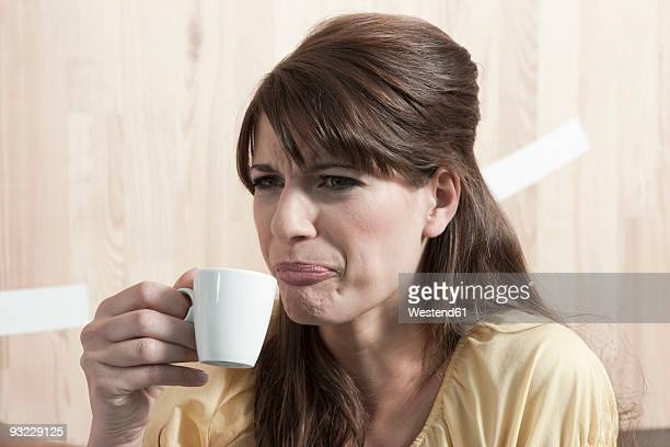 germany, cologne, young woman holding cup of coffee, portrait - negative emotion stock pictures, royalty-free photos & images