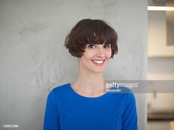 germany, cologne, young woman in kitchen, smiling, portrait - franja estilo de cabelo - fotografias e filmes do acervo