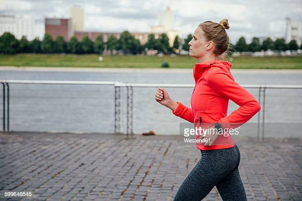 Germany, Cologne, young woman jogging at River Rhine