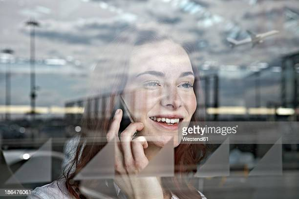 Germany, Cologne, Young woman on phone at airport