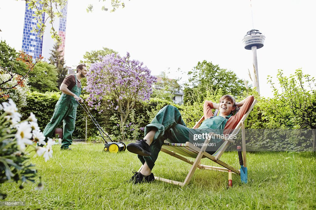 Germany, Cologne, Young woman relaxing on deck chair while man mowing lawn : Stock Photo