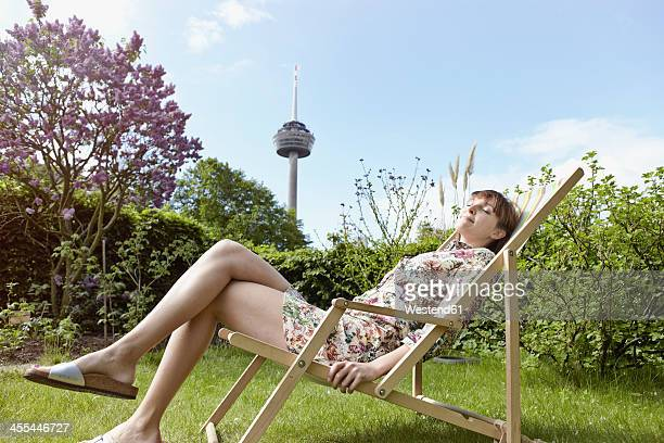 Germany, Cologne, Young woman relaxing on deckchair in garden