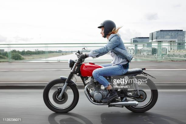germany, cologne, young woman riding motorcycle on bridge - hoofddeksel stockfoto's en -beelden