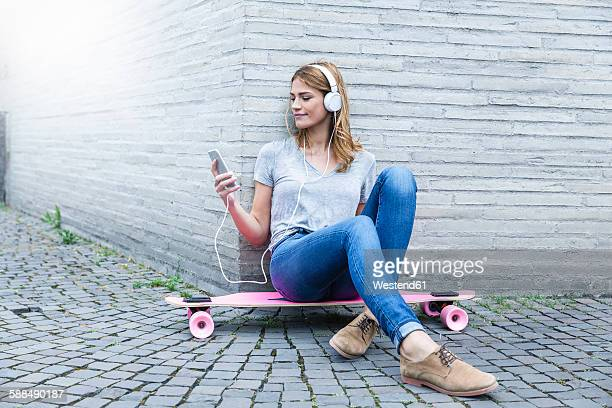 Germany, Cologne, young woman sitting on pink skateboard hearing music with headphones