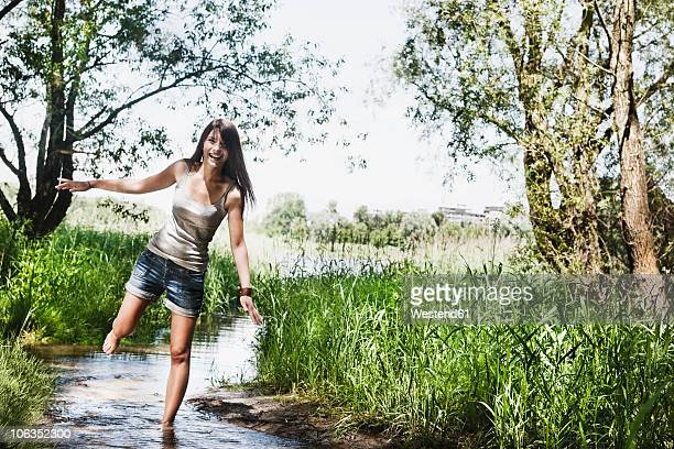Germany, Cologne, Young woman standing in creek