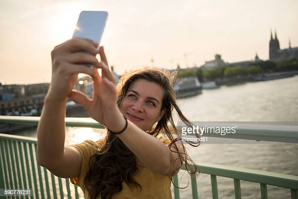Germany, Cologne, young woman standing on Rhine bridge taking a selfie with her smartphone