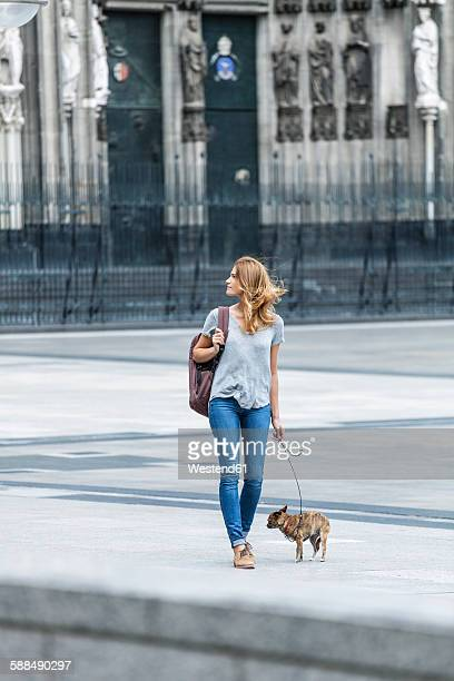 Germany, Cologne, young woman walking with her little dog in front of Cologne Cathredral