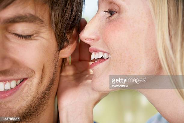 Germany, Cologne, Young woman whispering to man, close up