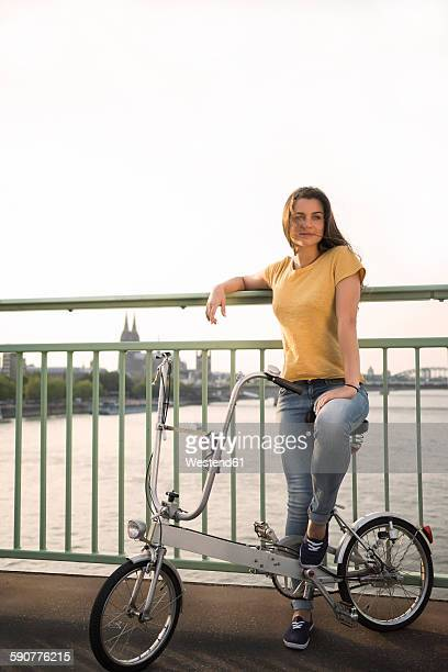 Germany, Cologne, young woman with bicycle standing on Rhine bridge