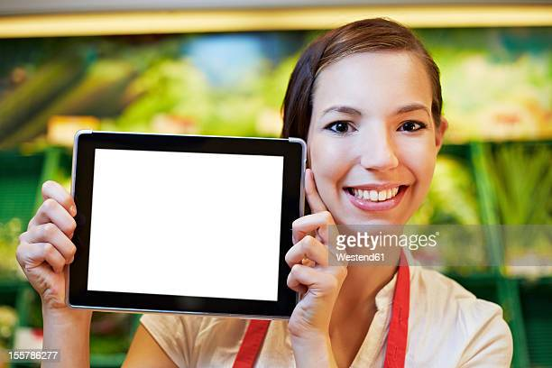 Germany, Cologne, Young woman with digital table in supermarket