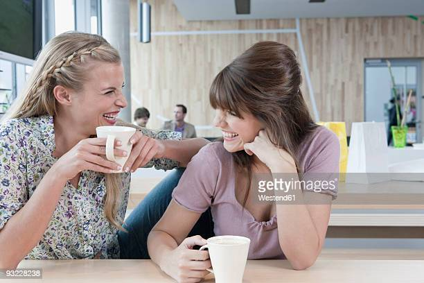 Germany, Cologne, Young women in cafe, laughing