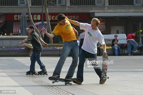 Germany, Cologne: Youth in their free time.- Young men skateboarding on the square in front of the cathedral.