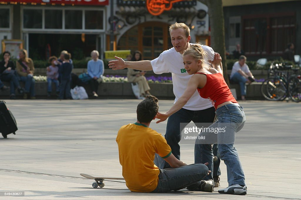 DEU, Germany, Cologne: Youth in their free time.- Young men skateboarding on the square in front of the cathedral; argument after a fall. A young woman trys to settle. : News Photo