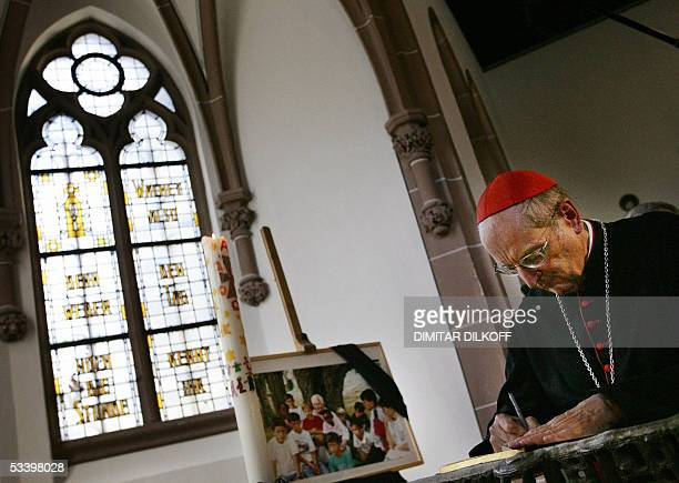 Cologne's Archbishop Cardinal Joachim Meisner writes in the guest book during a memorial service for the founder of the French religious Taize group...