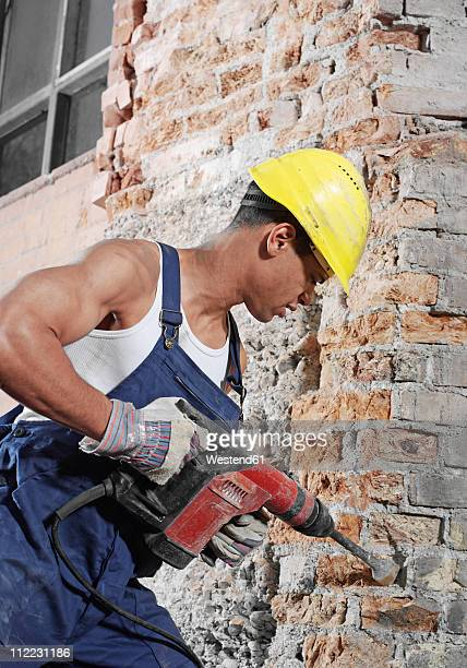 Germany, Construction worker working with drill machine