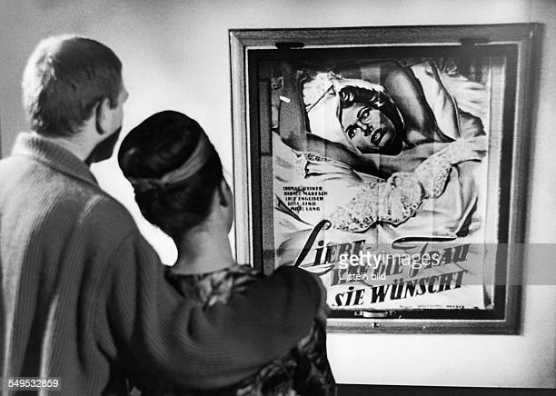 Couple looking at a film poster 1957