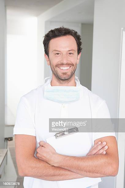 Germany, Dentist holding clip board, smiling, portrait
