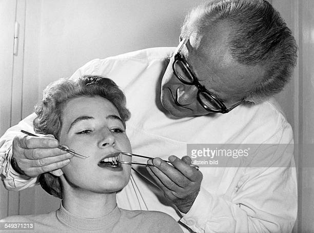 Germany dentist inspecting teeth of a woman in the fifties