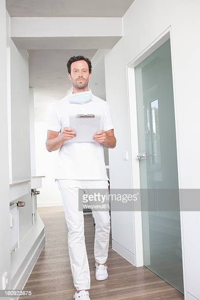 Germany, Dentist walking with clip board
