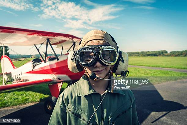 Germany, Dierdorf, Boy in front of biplane wearing old pilot outfit