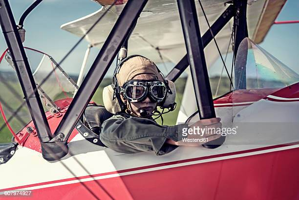 Germany, Dierdorf, Boy sitting in biplane wearing old pilot outfit