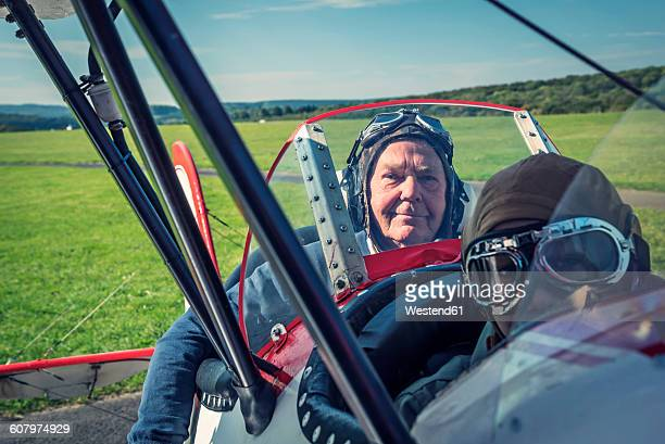Germany, Dierdorf, Grandfather and grandson sitting on old biplane