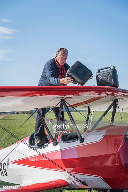 Germany, Dierdorf, Senior man standing on biplane with petrol canisters