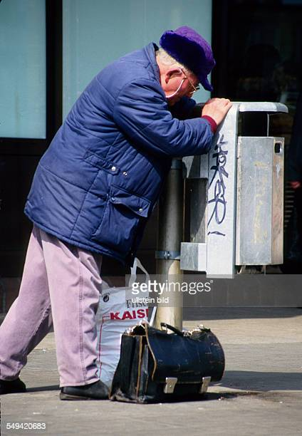 Germany, Dortmund, 1996: Poverty in Germmany.- An old man collecting deposit bottles out of a dustbin.