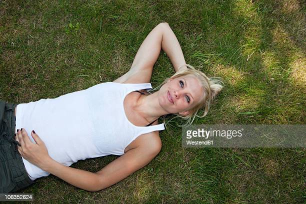 Germany, Dortmund, Young woman resting on grass, smiling