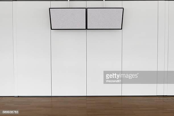 Germany, Duesselddorf, two flatscreen monitors on a wall at university