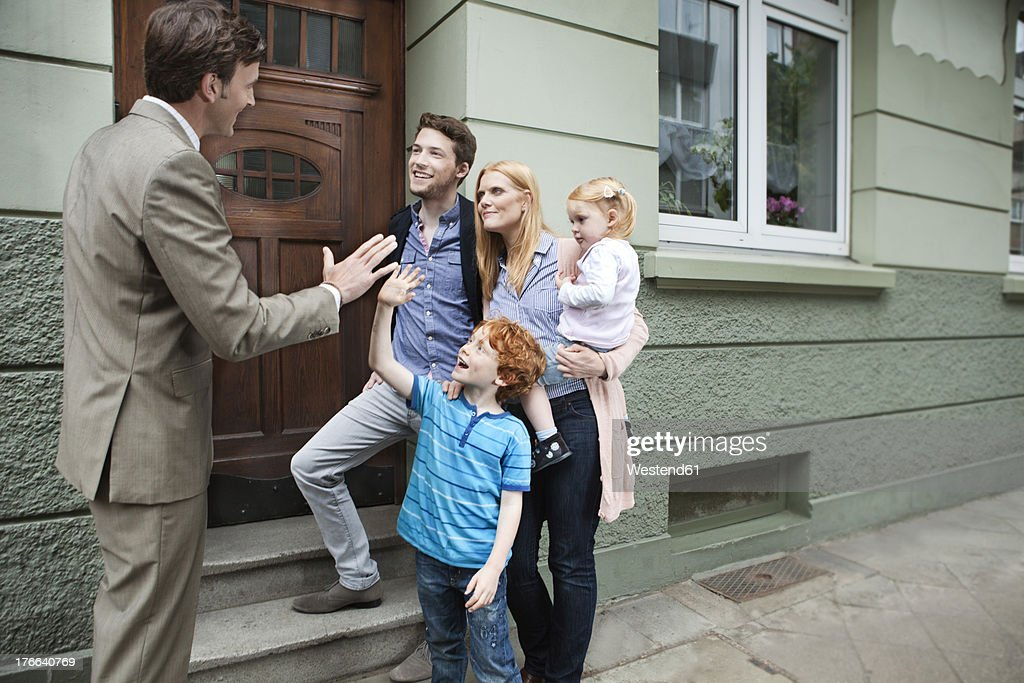Germany, Duesseldorf, Boy giving high five to estate agent and family standing in background : Stock Photo