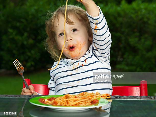 Germany, Duesseldorf, Girl sitting outside and eating noodles
