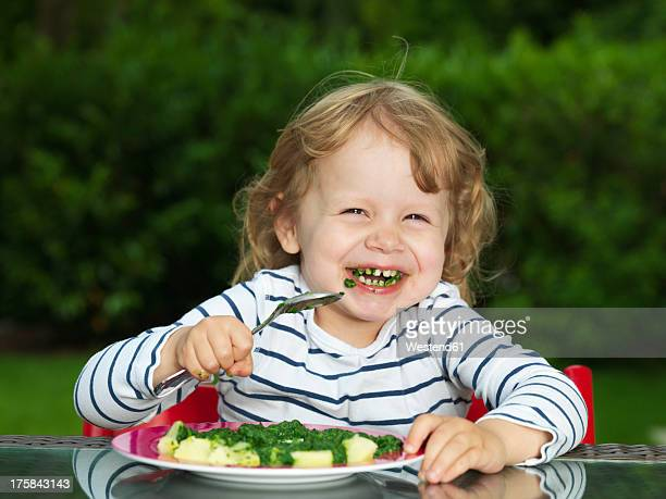 Germany, Duesseldorf, Girl sitting outside and eating spinach, smiling, portrait