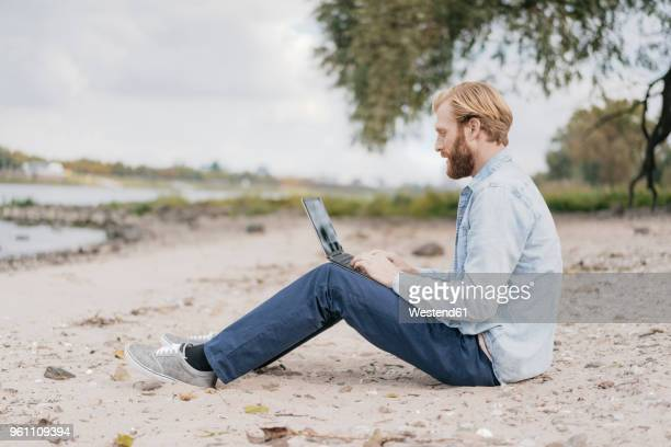 Germany, Duesseldorf, man sitting on the beach using laptop