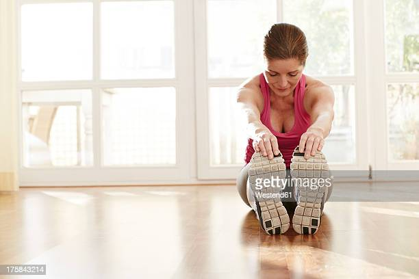 germany, duesseldorf, mature woman exercising at home - older woman bending over stock pictures, royalty-free photos & images