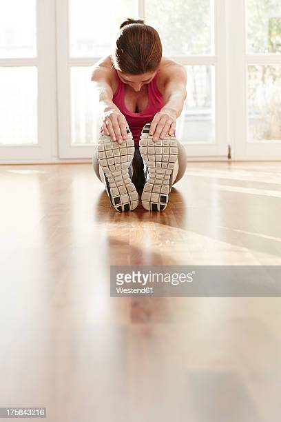 germany, duesseldorf, mature woman exercising at home - bend over cleavage stock photos and pictures