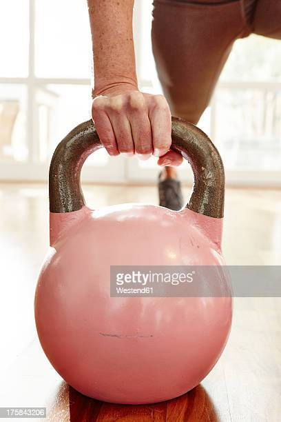 Germany, Duesseldorf, Mature woman exercising with kettlebell
