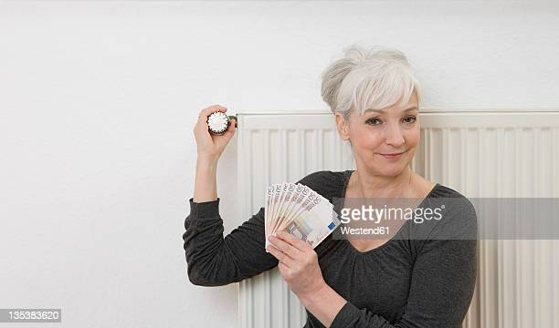 germany, duesseldorf, woman holding banknotes and adjusting heater at home, smiling, portrait - monetary policy stock pictures, royalty-free photos & images