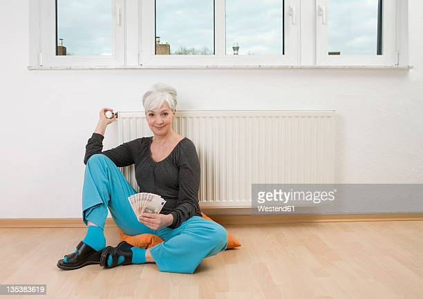 germany, duesseldorf, woman holding banknotes near heater at home, smiling, portrait - monetary policy stock pictures, royalty-free photos & images