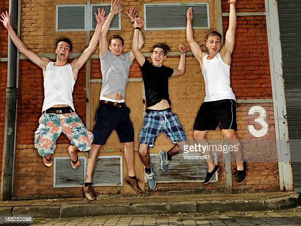 Germany, Duesseldorf, Young friends jumping in industrial area