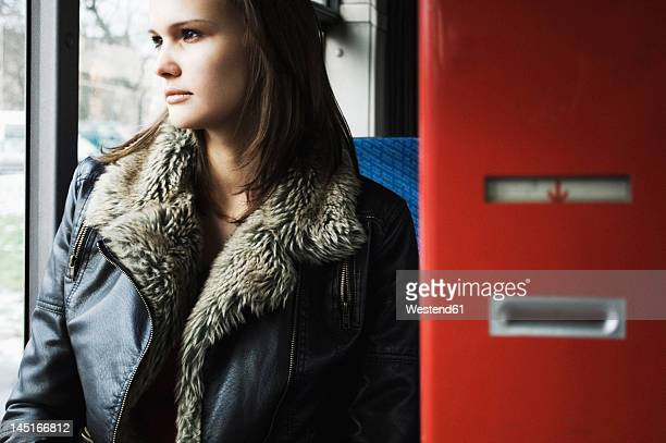 Germany, Duesseldorf, Young woman in public bus