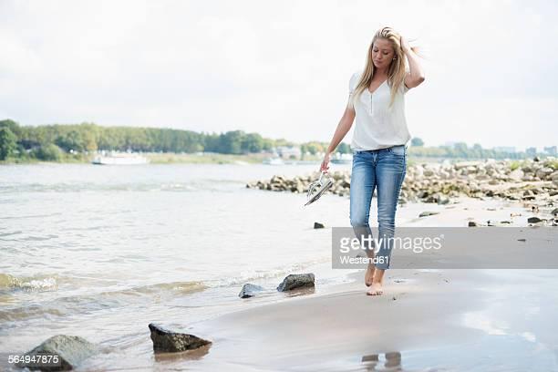Germany, Duesseldorf, young woman walking along riverside of Rhine