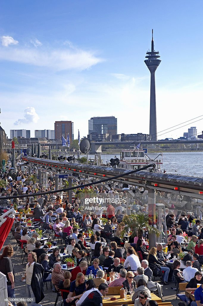 Germany, Dusseldorf, people at outdoor cafe and skyline : Stockfoto