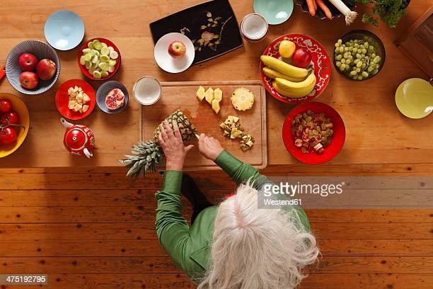 Germany, Dusseldorf, Senior woman preparing raw food