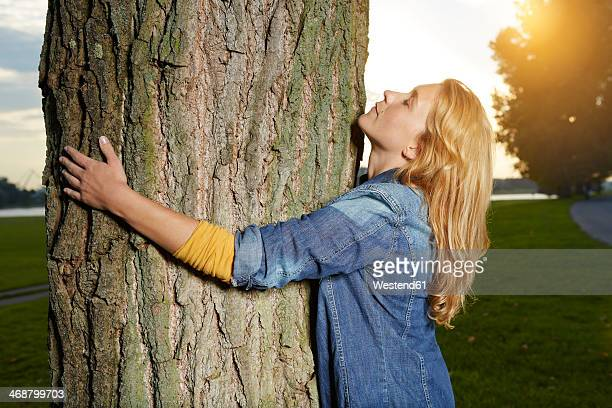 germany, dusseldorf, young woman hugging tree - tree hugging stock pictures, royalty-free photos & images