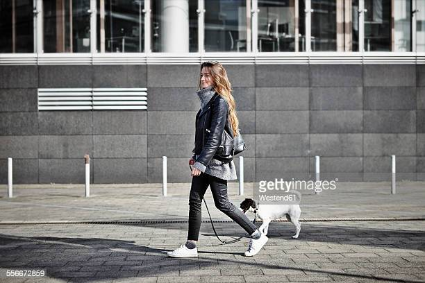 germany, dusseldorf, young woman walking her dog - andando - fotografias e filmes do acervo